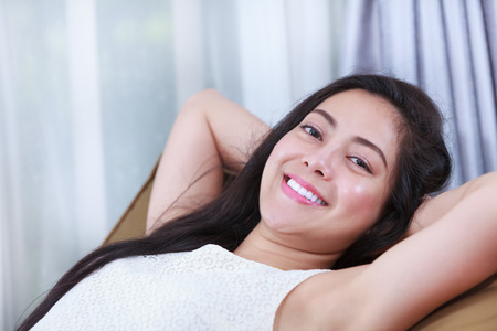 comfortable: Relaxing woman lie down comfortable and smiling happy looking at camera. Resting young asian female clasping her hands behind her nape of the neck. Stock Photo