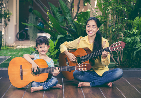 Happy family spending time together at home. Asian mother with daughter playing classic guitar and looking at camera. Vintage picture style. Positive human emotion.