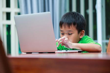 modern generation: Happy asian child. Handsome boy enjoying modern generation technologies playing indoors using laptop computer and mobile phone. Education and learning concept.