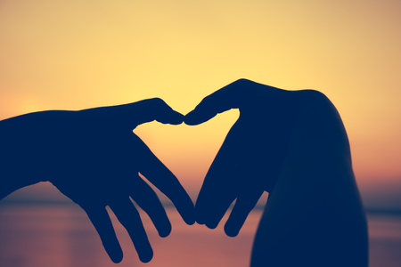 sky metaphor: Concept heart shape or symbol made of human hand silhouette on colorful sunset sky background. Metaphor to love, valentine, romantic, couple ,wedding, romance, summer or sunrise. Stock Photo