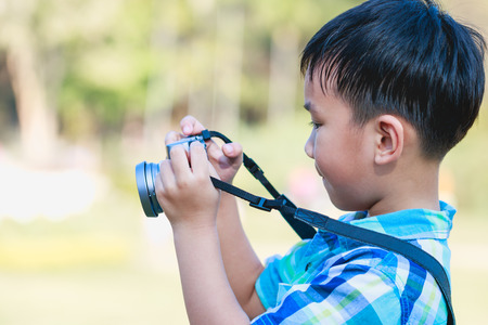 pursuing: Handsome asian boy taking photo by vintage film camera on blurred nature background, on summer in the day time. Child in nature, outdoors. Active lifestyle, curiosity, pursuing a hobby concept.