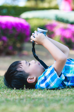 pursuing: Handsome asian boy taking photo by vintage film camera, exploring nature at park, on summer in the day time. Child in nature, outdoors portrait. Active lifestyle, curiosity, pursuing a hobby concept. Stock Photo