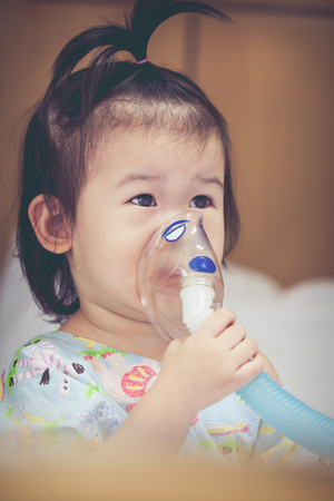 inhalator: Cute asian child holds a mask vapor inhaler for treatment of asthma on sickbed in hospital. Breathing through a steam nebulizer. Concept of inhalation therapy apparatus. Vintage tone.