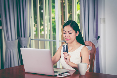 cross process: Beautiful asian woman holding credit card and making order at home. Young adult using laptop computer for shopping on internet. Online shopping concept. Cross process and vintage tone.