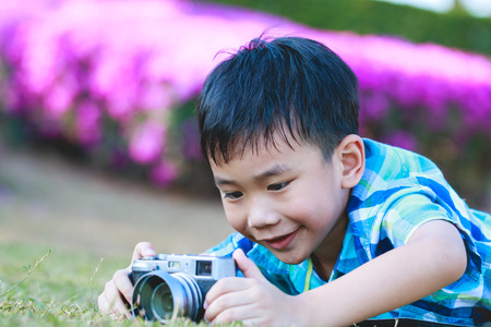 pursuing: Asian boy taking photo by vintage film camera on blurred nature background at the day time.