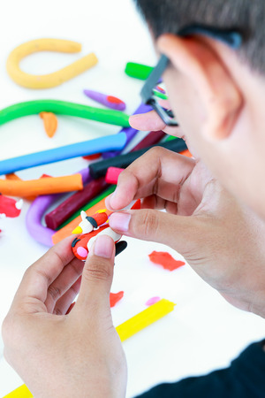 strengthen: Close up. Child playing and creating toys  . Selective focus, model clay in focus. Strengthen the imagination of child. Stock Photo