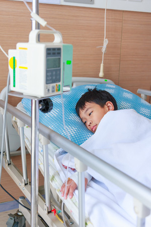 sickbed: Illness asian boy lying on sickbed in hospital with infusion pump intravenous IV drip. Shallow depth of field (DOF) child in focus, IV machine out of focus. Health care and medical concept.