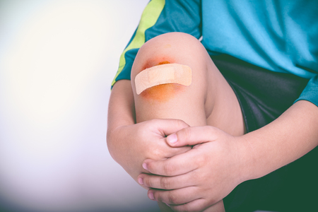 injurious: Athlete child injured. Child knee with a plaster and bruise. Selective focus, wound in focus. Human health care and medicine concept. Vintage style.