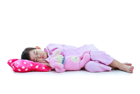 dream body: Full body. Healthy children concept. Asian child sleeping peacefully. Adorable girl in pink pajamas taking a nap. Isolated on white background.