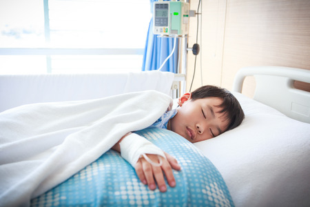 sickbed: Illness asian boy sleeping at modern and comfortable equipped hospital room with saline intravenous (IV) on hand. Health care and people concept.