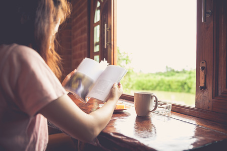 country life: Lifestyle of woman reading a book and enjoy fresh coffee or tea in the morning at home. Sun is shining into the room. Light shines through the window. Happy time of country life. Vintage tone. Stock Photo