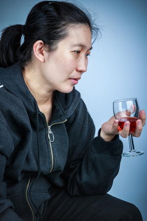 don't care: Side view of  asian woman with alcohol. Concept about human dont care for health. Vignette and low key picture style.