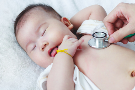 sickbed: Professional pediatrician examining infant. Doctor using a stethoscope to listen to kids chest checking heartbeat. Two months baby asian girl lying on sickbed in hospital. Stock Photo