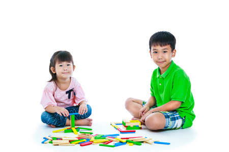 Happy asian children. Boy and girl playing toy wood blocks, isolated on white background. Educational toys for elementary and kindergarten child. Strengthen the imagination of child. Studio shot.