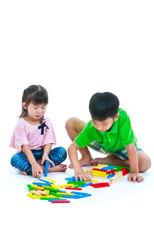 Asian children playing toy wood blocks together. Frustrated girl crying and showing moody behavior. Isolated on white background. Educational toys for elementary and kindergarten child. Studio shot.
