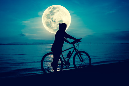 cross process: Silhouette of bicyclist in action enjoying the view at seaside on bright full moon sky background. Active outdoors lifestyle for healthy concept. Cross process. The moon were NOT furnished by NASA.