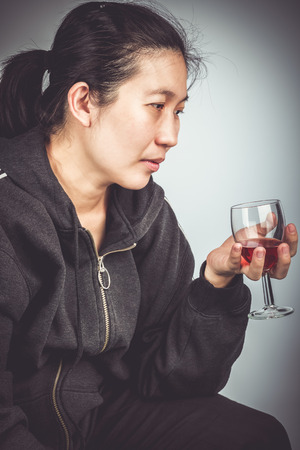 don't care: Side view of  asian woman with alcohol. Concept about human dont care for health. Vignette and vintage picture style. Stock Photo