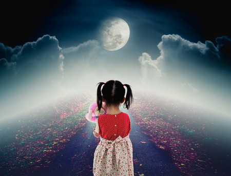 nightly: Back view of lonely child with doll sad gesture on pathway with a nightly sky and a large moon for halloween background. The moon were NOT furnished by NASA. Stock Photo