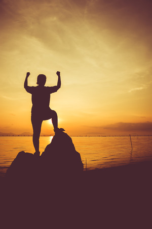 arm up: Silhouette of successful woman relax and showing arm up gesture. Action of winner. Vignette and vintage picture style. Stock Photo