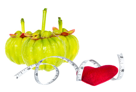 citric: Garcinia cambogia fresh fruit with red heart and measuring tape, isolated on white. Garcinia is spice plants. It helps in the metabolism contain high vitamin C and hydroxy citric acids for weight loss