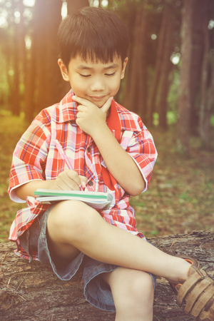 resolve: Happy asian boy can resolve problem at park. Outdoors in the day time with bright sunlight. Children planning and education concept. Warm tone and vintage picture style.