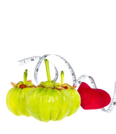citric: Garcinia cambogia fresh fruit with red heart and measuring tape, isolated on white. Garcinia is spice plants, contain high vitamin C and hydroxy citric acids for weight loss