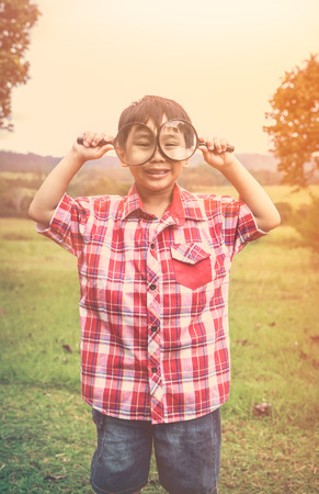 peers: Playful asian child enjoying at park on vacation. Young smart boy peers at camera through two magnifying glass on blurred nature background. Outdoors in the day time with bright sunlight. Warm tone. Stock Photo