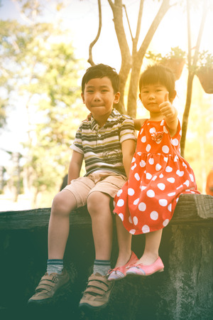 Happy asian siblings smiling and looking at camera on nature background. Children relaxing outdoors in the day time with sunlight, travel on vacation. Sister hand on her brother shoulder. Warm tone.