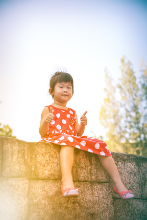 thump: Happy asian girl with thump up and looking at camera at park. Child relaxing outdoors in the day time with bright sunlight, travel on vacation. Positive human emotion.  Warm tone.