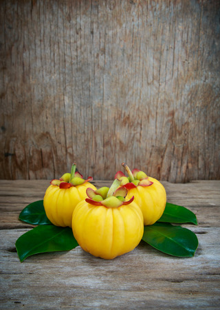 citric: Garcinia cambogia fresh fruit on wood background. Garcinia atroviridis is a spice plants and high vitamin C and hydroxy citric acids (HCA) for diet and good health.