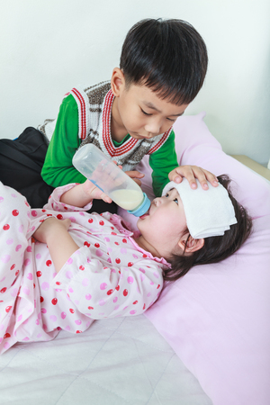 vigil: Sick sister lying and suck up milk on the bed, kindly brother keep vigil over a sick of closely. Conceptual image about loving and bonding of sibling. Happy family spending time together.