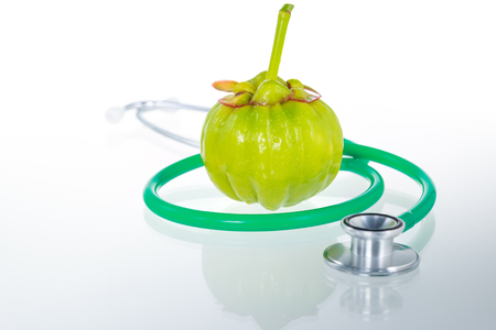 acids: Garcinia cambogia fresh fruit and stethoscope with reflection, isolated on white. Garcinia atroviridis is a spice plants and high vitamin C and hydroxy citric acids (HCA) for diet and good health. Stock Photo
