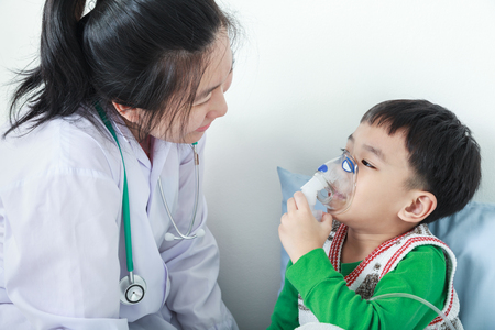 Happy child having respiratory illness helped by health professional with inhaler. Pediatrician take care asian boy with asthma problems making inhalation with mask on his face at hospital. Stock Photo