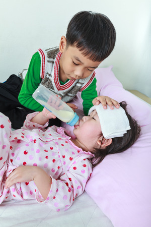 Sick sister lying and suck up milk on the bed, kindly brother keep vigil over a sick of closely. Conceptual image about loving and bonding of sibling.