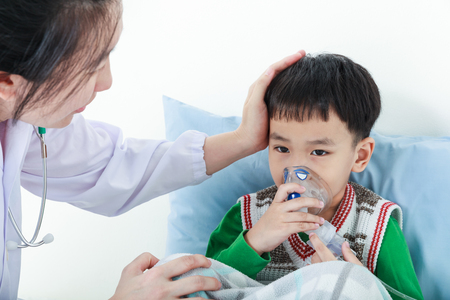 Sad child having respiratory illness helped by health professional with inhaler. Pediatrician take care asian boy with asthma problems making inhalation with mask on his face at hospital. Stock Photo