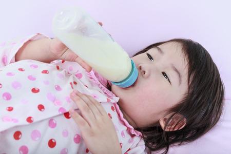 nursing bottle: Closeup cute asian girl sucking up milk bottle in bed. Drinking milk for good health.