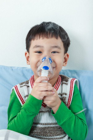 sickbed: Happy asian child holds a mask vapor inhaler for treatment of asthma on sickbed in hospital. Breathing through a steam nebulizer. Concept of inhalation therapy apparatus.