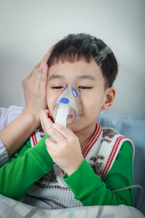 Sad asian child holds a mask vapor inhaler for treatment of asthma on sickbed in hospital. Breathing through a steam nebulizer. Concept of inhalation therapy apparatus. Stock Photo