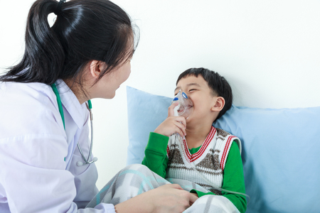 Happy child having respiratory illness helped by health professional with inhaler. Pediatrician take care asian boy with asthma problems making inhalation with mask on his face at hospital. Фото со стока