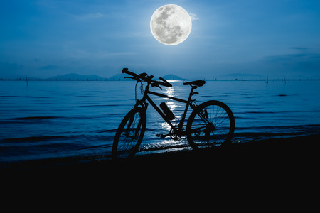 not full: Silhouette of bicycle on the beach against beautiful full moon in the sea, blue sky background. Outdoors. The moon were NOT furnished by NASA.