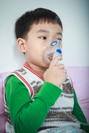 sickbed: Sad asian child holds a mask vapor inhaler for treatment of asthma on sickbed in hospital. Breathing through a steam nebulizer. Concept of inhalation therapy apparatus. Vignette style.