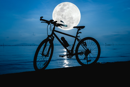 Silhouette of bicycle on the beach against beautiful full moon in the sea, blue sky background. Outdoors. The moon were NOT furnished by NASA.