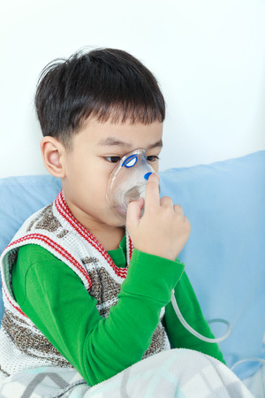 sickbed: Sad asian child holds a mask vapor inhaler for treatment of asthma on sickbed in hospital. Breathing through a steam nebulizer. Concept of inhalation therapy apparatus. Stock Photo