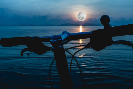 not full: Silhouette of a parts bicycle, handlebar on the beach against beautiful moonlight in the sea, blue sky background. Reflection of full moon in water. Outdoors. The moon were NOT furnished by NASA.