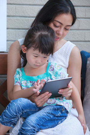 child finger: Asian girl using digital tablet with her mother near by. Child finger point at tablet. Family spending time together at home. Concept about education by e-learning.