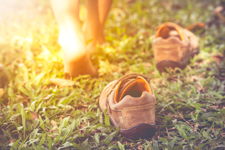 Child take off leather shoes. Close up child's foot learns to walk on grass, reflexology massage. Kid relax in garden with sunlight. Shallow depth of field (dof), selective focus. Retro style. Banque d'images