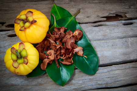 Top view. Garcinia cambogia fresh fruit on wood background. Dry garcinia on leaf. Garcinia atroviridis is a spice plants and high vitamin C and hydroxy citric acids (HCA) for diet and good health. Stock Photo