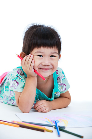 strengthen: Pretty asian girl lie on the floor looking at camera and smiling. Concepts of creativity and education, strengthen the imagination of child. Studio shot. Isolated on white background. Stock Photo