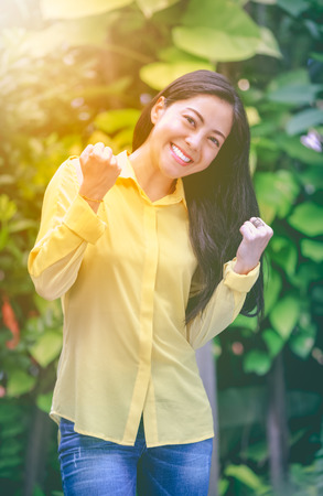 Asian woman smiling happy in park. Pretty young woman outdoors with bright sunlight. Positive human emotion. Action of winner or successful people.