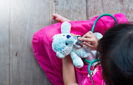 plush toy: Top view of child playing doctor or nurse with plush toy bear at home. Happy girl listens a stethoscope to toy. Playful girl role playing. Stock Photo